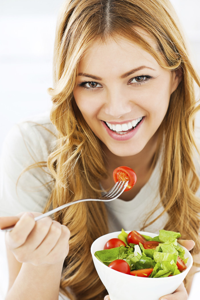 Close-up of woman eating a salad.